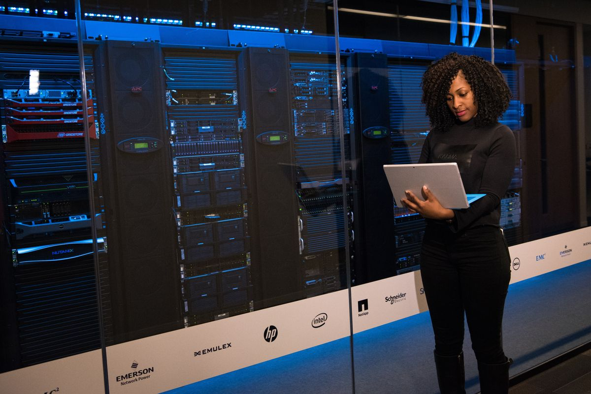 Woman standing while holding laptop in front of server rack. Maybe doing database queries :)